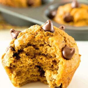 A chocolate chip pumpkin muffin with a bite out of it on a white counter in front of a muffin tin of pumpkin muffins