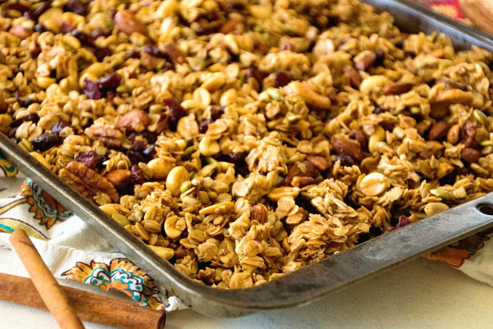Granola spread out on baking sheet on a napkin with cinnamon sticks next to it.