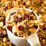 White mug of homemade pumpkin spice granola sitting in a pile of granola