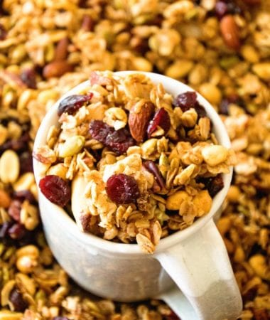 Pumpkin granola in a white mug sitting in a pile of pumpkin spice granola