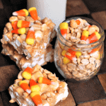 Three candy corn peanut mallow bars on a wood board with a glass jar of peanuts and candy corn and a glass of milk