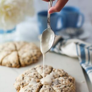 Hand holding a spoon of frosting over chocolate chip toffee scones on a white counter