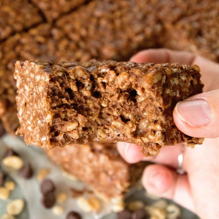 Hand holding a chocolate peanut butter rice krispies bar with a bite out of it