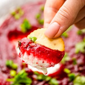 Hand holding cracker with cranberry dip on it