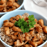 Two blue bowls of crock pot chicken teriyaki on rice