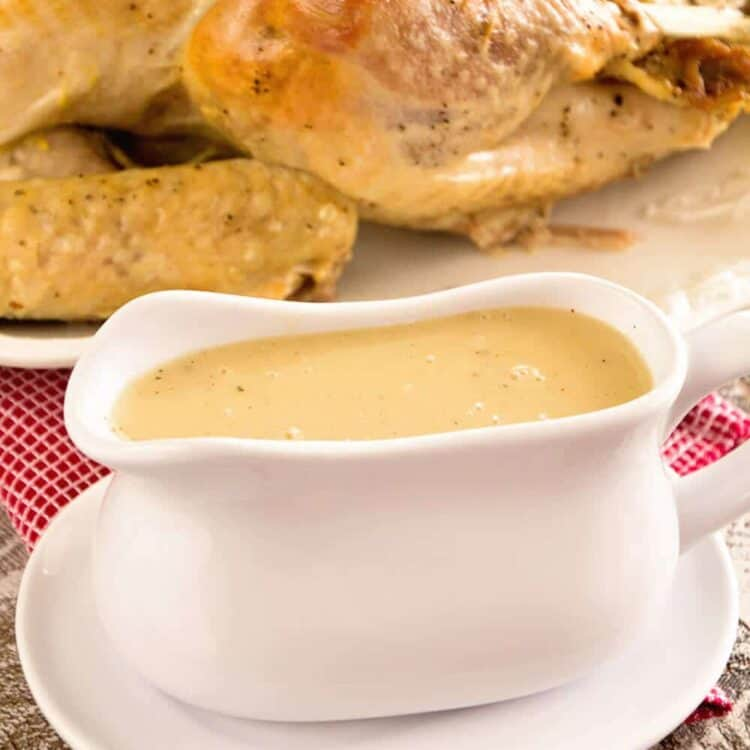 A white gravy boat of easy homemade gravy in front of a cooked turkey