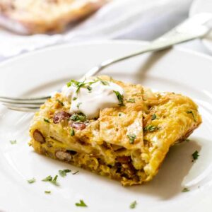 Piece of green chile breakfast enchilada casserole with sour cream on a white plate with a fork