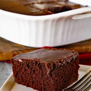 Piece of homemade chocolate cake with chocolate frosting on a white plate with a fork in front of a white baking dish containing the rest of the cake