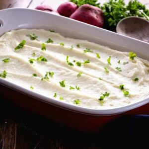 White baking dish of mashed potatoes on a table with red potatoes, a wooden spoon, and fresh parsley