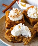 Pumpkin Bars topped with whipped cream on plate