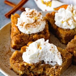 Four pumpkin pie bars on a plate topped with whipped cream and cinnamon with the front bar having a bite out of it