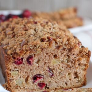 A partially sliced loaf of Apple Cranberry Bread