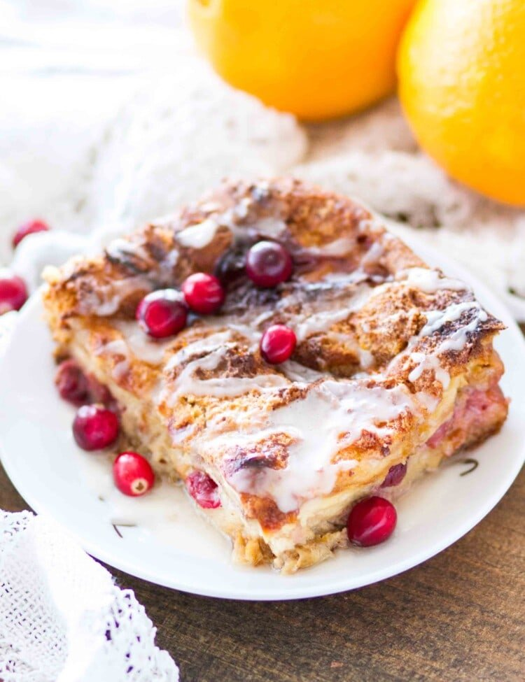 A large slice of cranberry orange bread pudding topped with icing on a white plate with cranberries