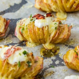 Hasselback potatoes on a parchment paper lined baking sheet