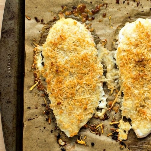 Two healthy parmesan crusted chicken breasts on a paper lined baking sheet