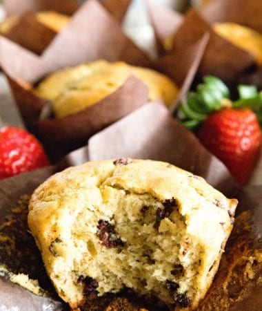 A chocolate chip muffins with a bite out of it sitting on a brown muffin liner