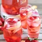 Three glasses and a pitcher of peach rose sangria on a wood table with slices of peach and strawberries