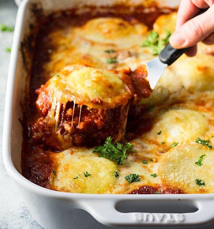 A spatula lifting a ravioli out of a white baking dish of ravioli lasagna