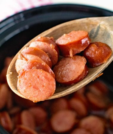 Crock Pot Glazed Kielbasa Bites on a wooden spoon being held over a crock pot