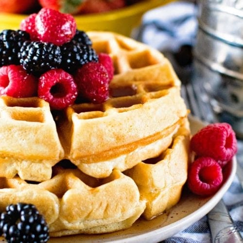 Two homemade waffles with raspberries and blackberries on a plate in front of a yellow bowl of strawberries