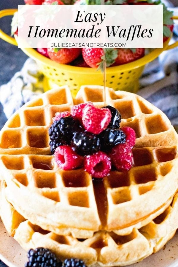 Syrup being poured over a stack of two waffles with berries on a plate