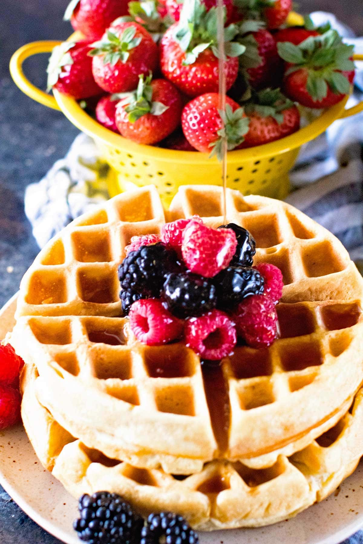 fluffy waffle recipe topped with fruit and drizzled with syrup.