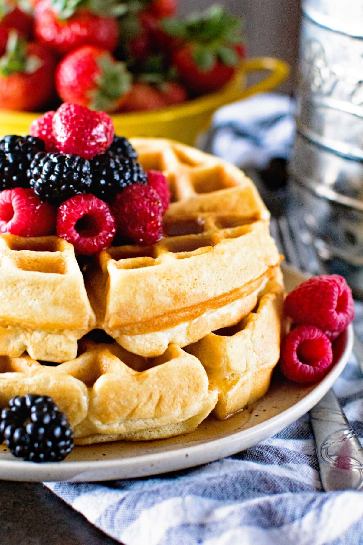 homemade waffle recipe topped with raspberries, blackberries and strawberries.