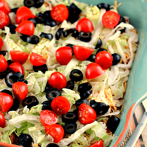 Easy taco dip in a square blue baking dish