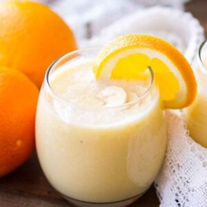 Glass of fresh orange smoothie with banana slices in it and an orange slice on the rim sitting on a wooden table with a white cloth and two oranges