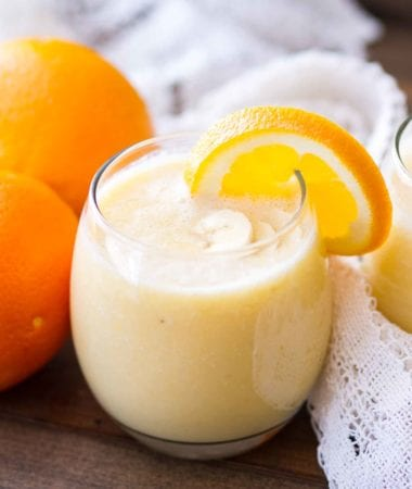 A glass of fresh orange smoothie with an orange slice on the rim next to two oranges