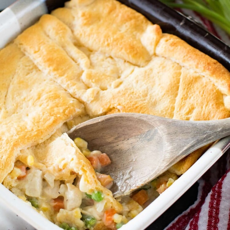 A square baking dish of easy chicken pot pie casserole with a wooden spoon in it