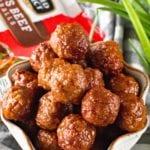 Meatballs with Grape Jelly and Chili Sauce in a white bowl on a grey and white striped towel