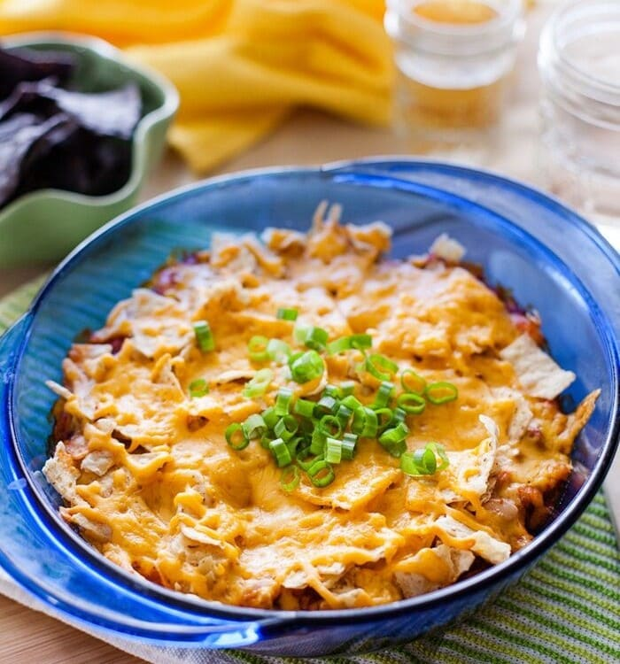 Mexican casserole in a blue glass dish on a green towel