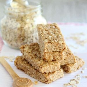 A pyramid of no bake peanut butter honey granola bars on a white plastic cutting board along with oats, a glass jar of oats, and a small wood spoon full of peanut butter