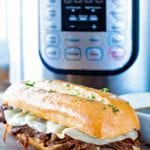 French Dip Sandwich in front of a Pressure Cooker