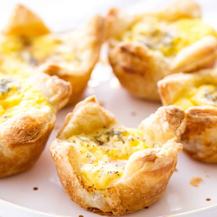 Quiche cups with ham and cheddar cheese on a white plate