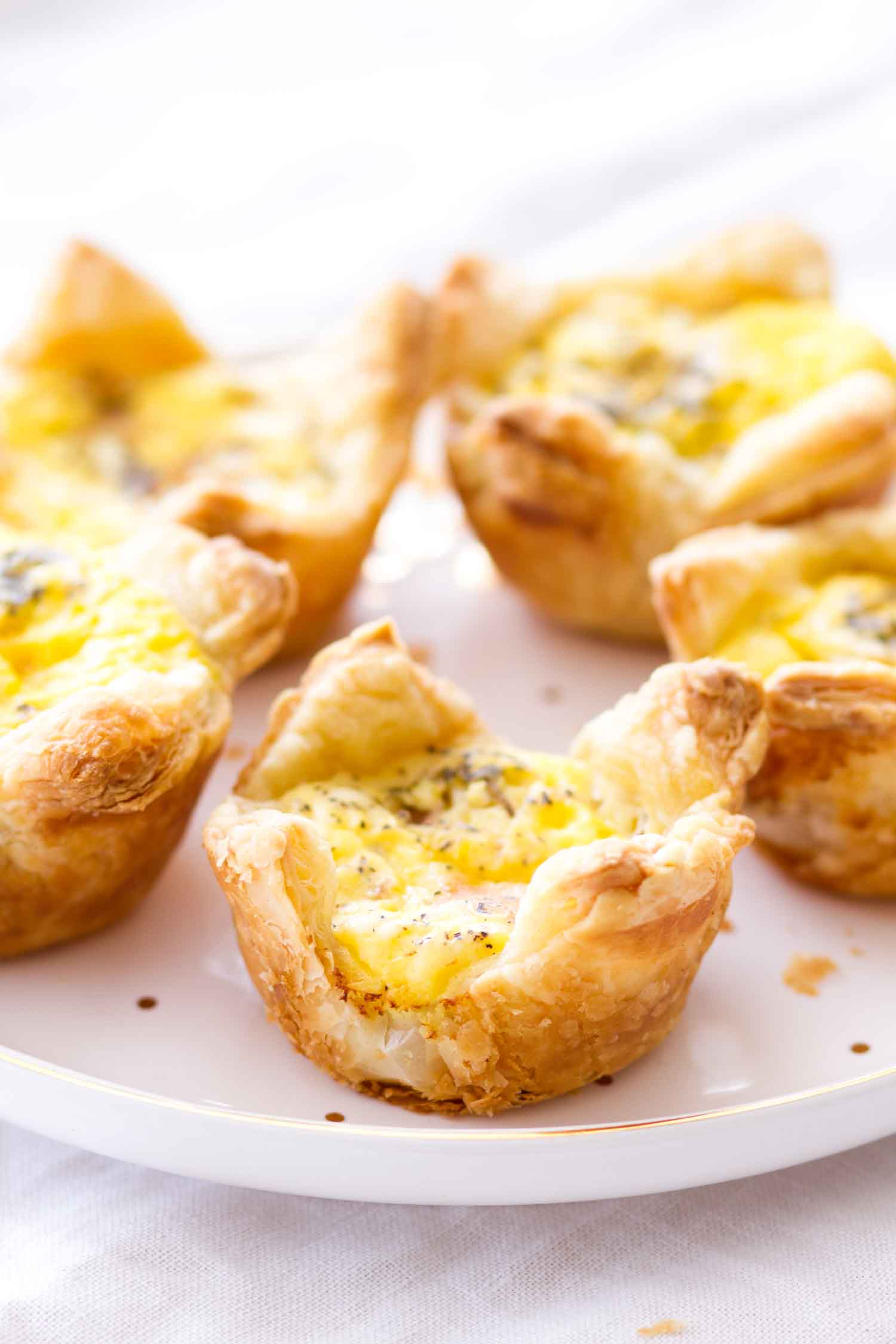 baked cheddar and ham quiche cups on white plate