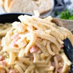 Chicken Cordon Bleu Noodle skillet on a wooden spoon being held over a skillet of pasta