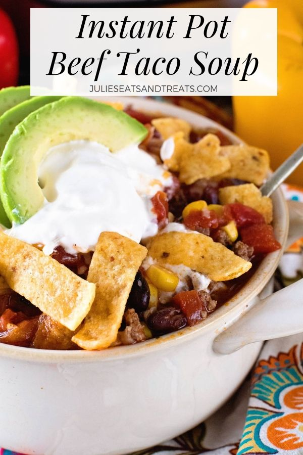 Instant pot beef taco soup in a large bowl topped with sour cream, frito chips, and avocado