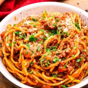 Bowl of spaghetti garnished with parmesan cheese and chopped parsley.