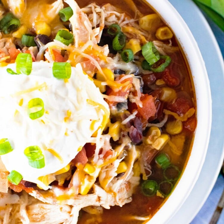 Chicken Taco Soup in a white bowl with sour cream and green onions on top