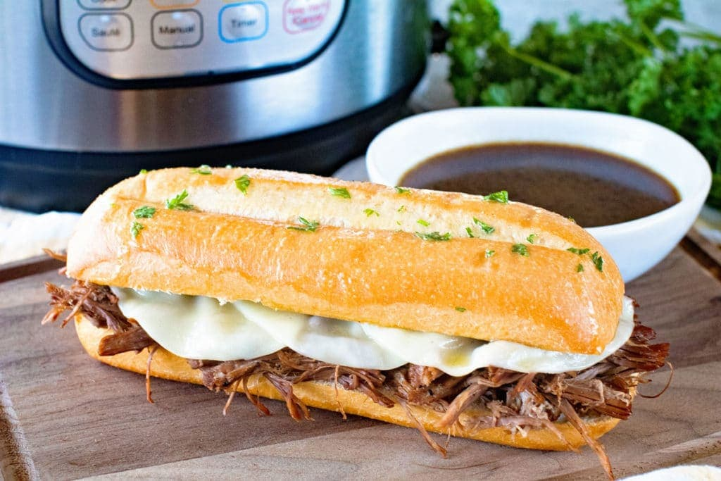 French Dip sandwich on wood cutting board with a white bowl of au jus behind it and an Instant Pot