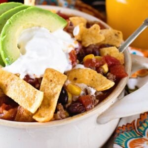 Taco Soup in a white bowl topped with fritos, sour cream, and avocado slices