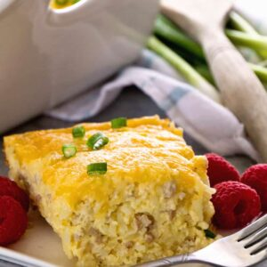 A piece of sausage cheese hash brown breakfast casserole on a white square plate with a fork and raspberries