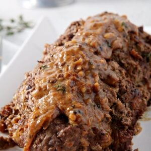 French Onion Meatloaf, sitting on a white platter, covered in gruyere gravy