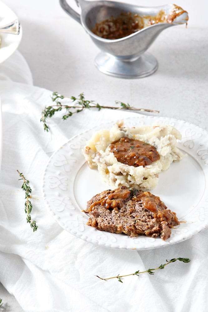 A slice of French Onion Meatloaf, covered in gravy, on a white plate with a serving of mashed potatoes and gravy, ready for eating