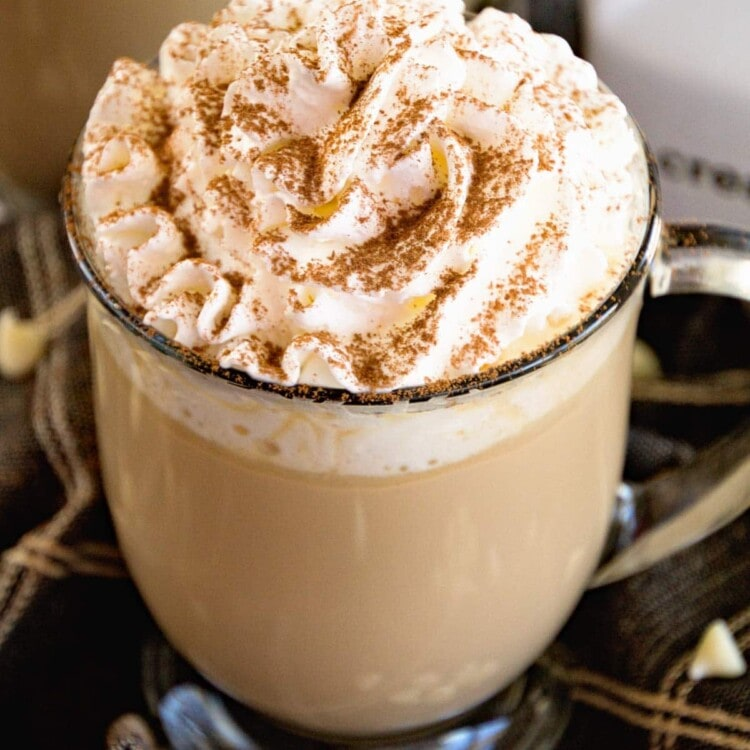 A clear glass mug of white chocolate latter topped with whipped cream and cinnamon