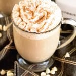 A clear glass mug of white chocolate latte with whipped cream and cinnamon on top sitting on a cloth napkin with white chocolate chips