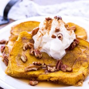 two slices of baked pumpkin french toast with syrup, pecans, and whipped cram on top on a white plate