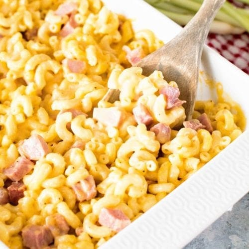 ham and cheese casserole with noodles in a white baking dish with a wood spoon in it
